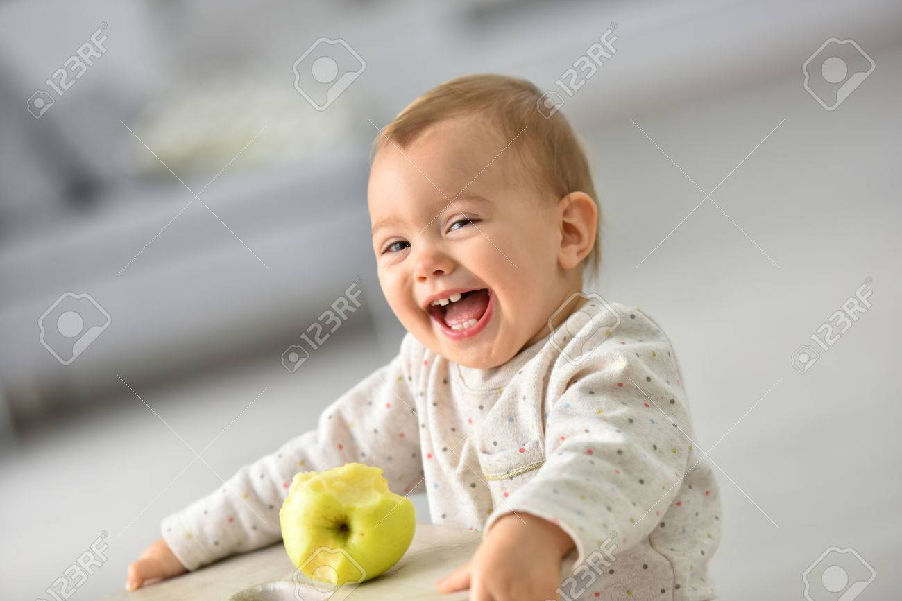Cute 15-month-old baby girl eating an apple Stock Photo - 47873034
