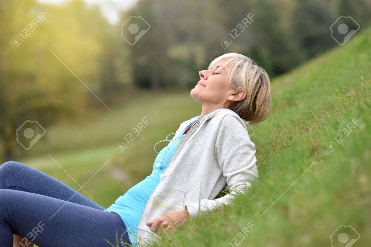Senior woman in fitness outfit relaxing in park - 48552370
