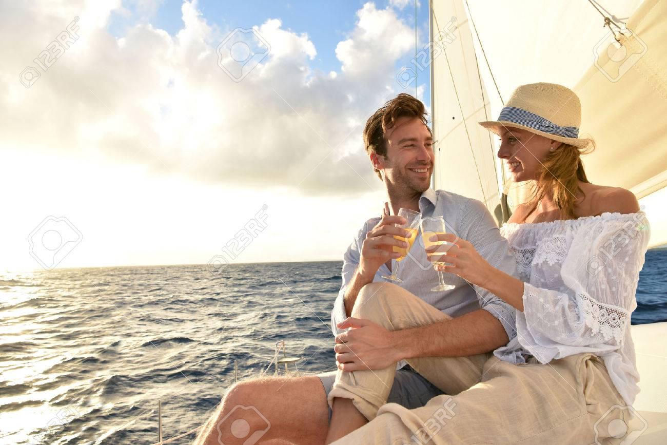 Romantic couple cheering on sailboat at sunset - 50055751