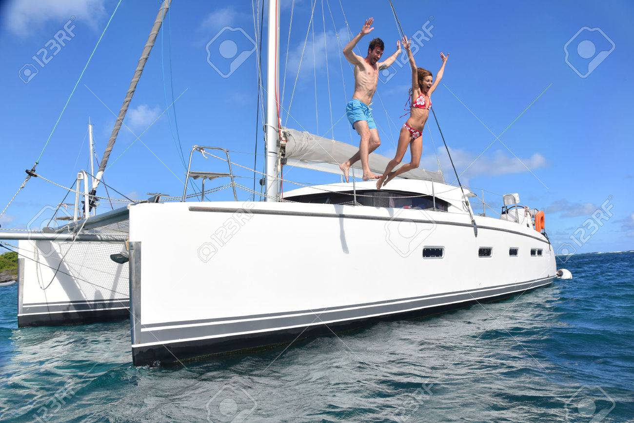 Cheerful couple jumping into water from boat - 50065467