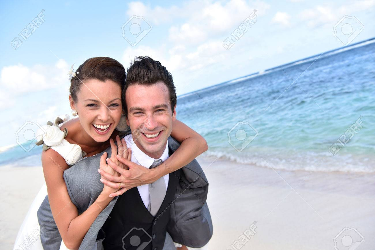 Groom giving piggyback ride to bride at the beach - 50065490