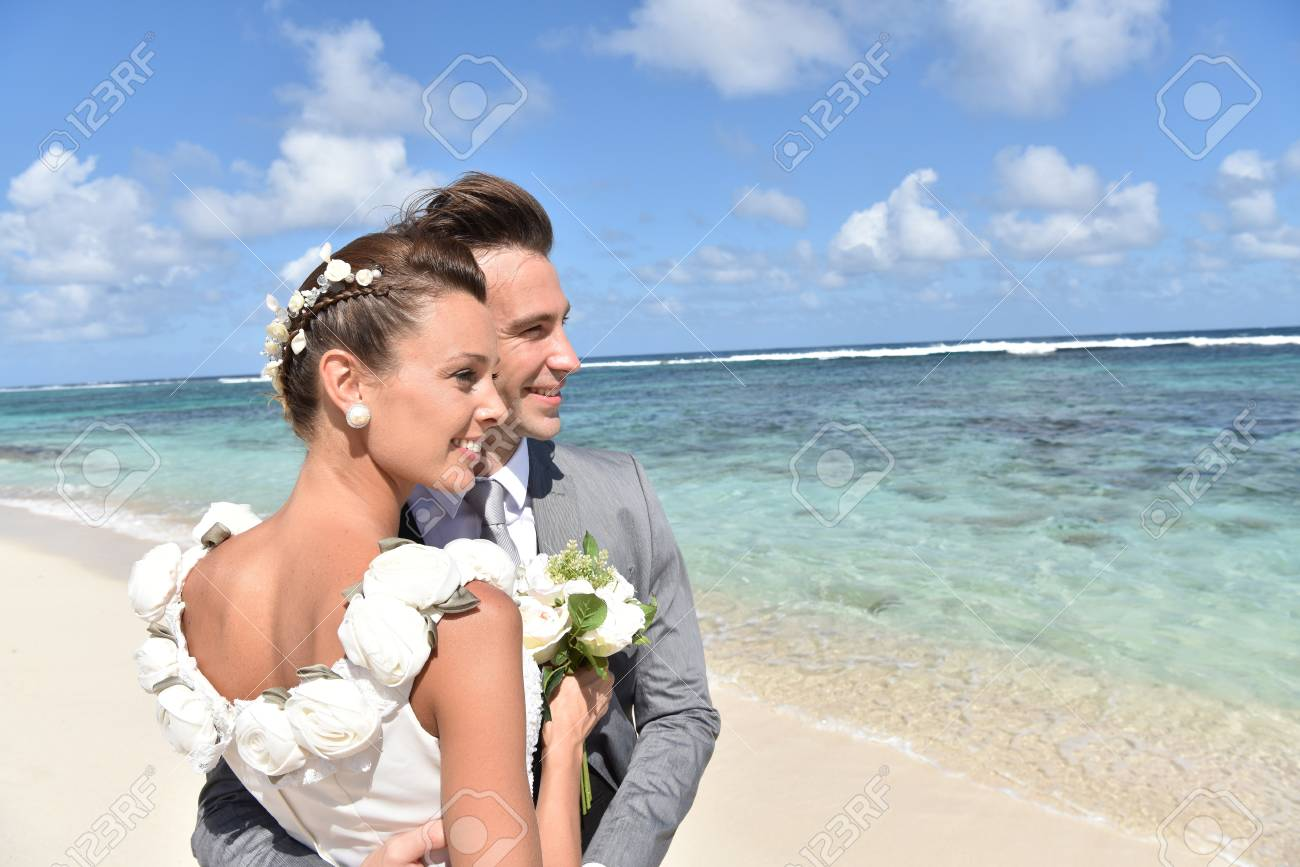 Just married couple on the beach looking towards the skyline - 50065556