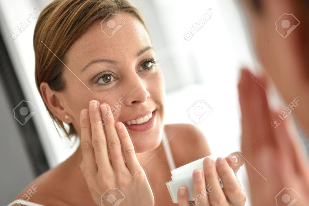 Woman applying facial cream on her face Banque d'images - 50065580