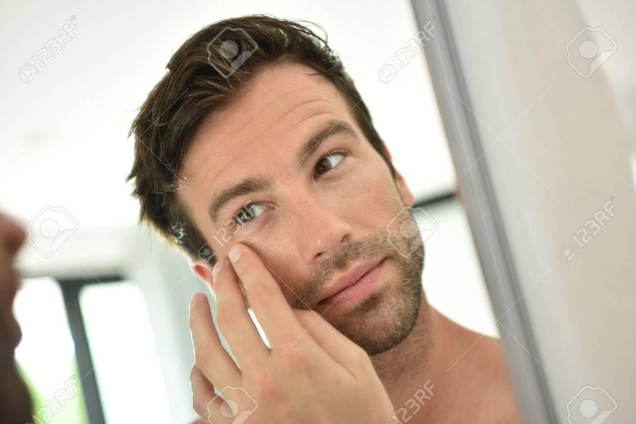 Bel homme d'appliquer la crème du visage dans le miroir Banque d'images - 50065597