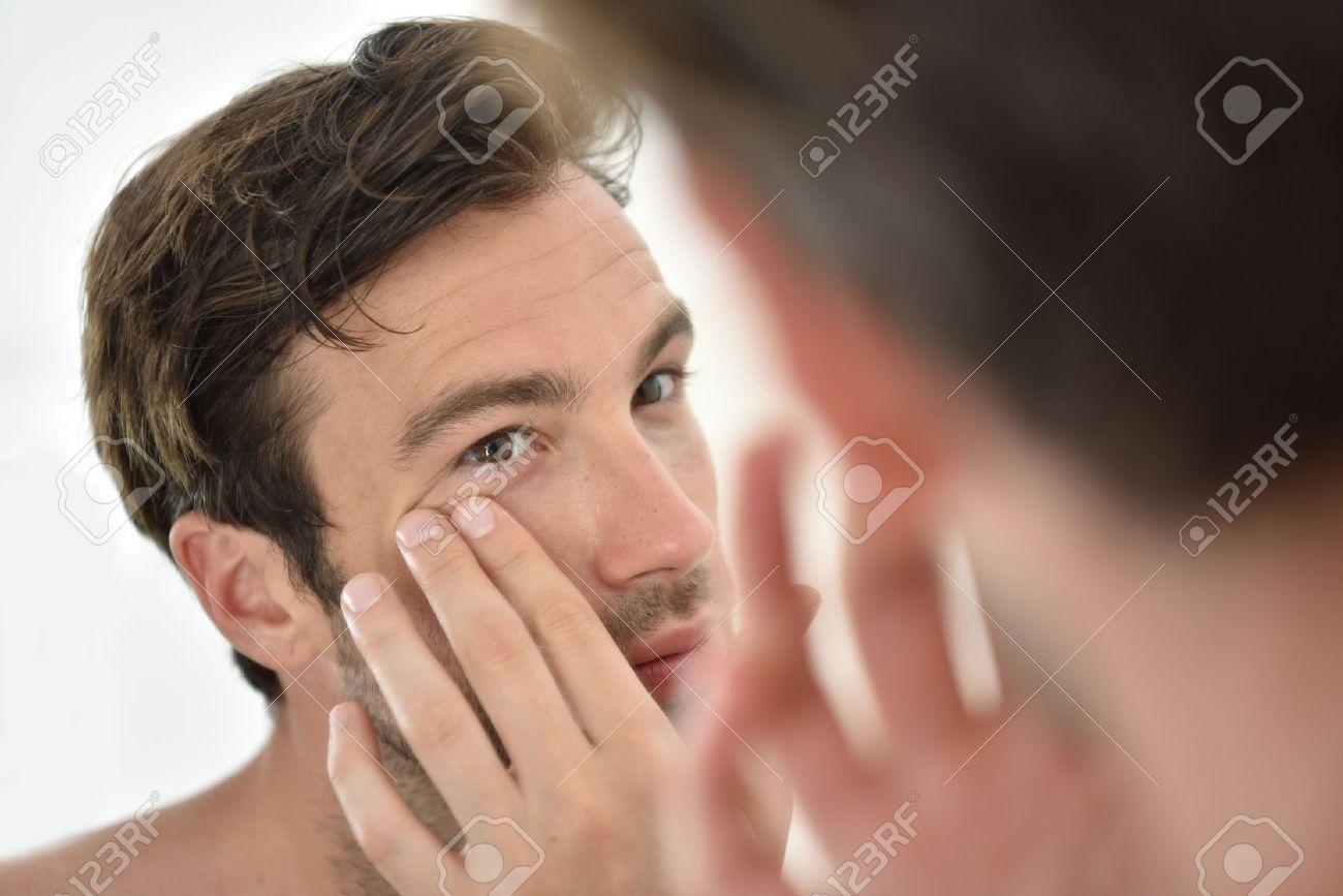 Bel homme d'appliquer la crème du visage dans le miroir Banque d'images - 50065599