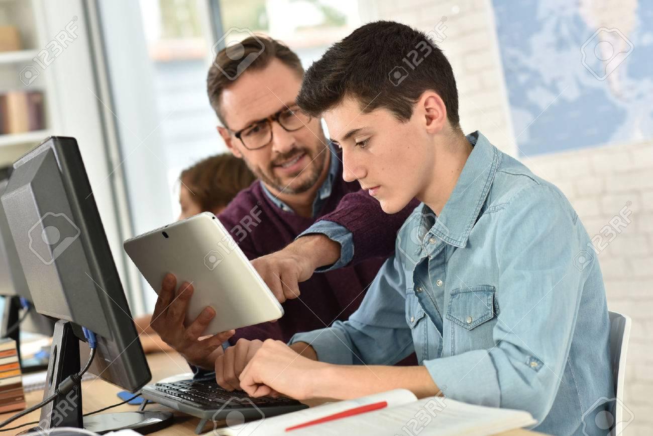 Enseignant en classe informatique aider adolescent avec tablette Banque d'images - 50630577