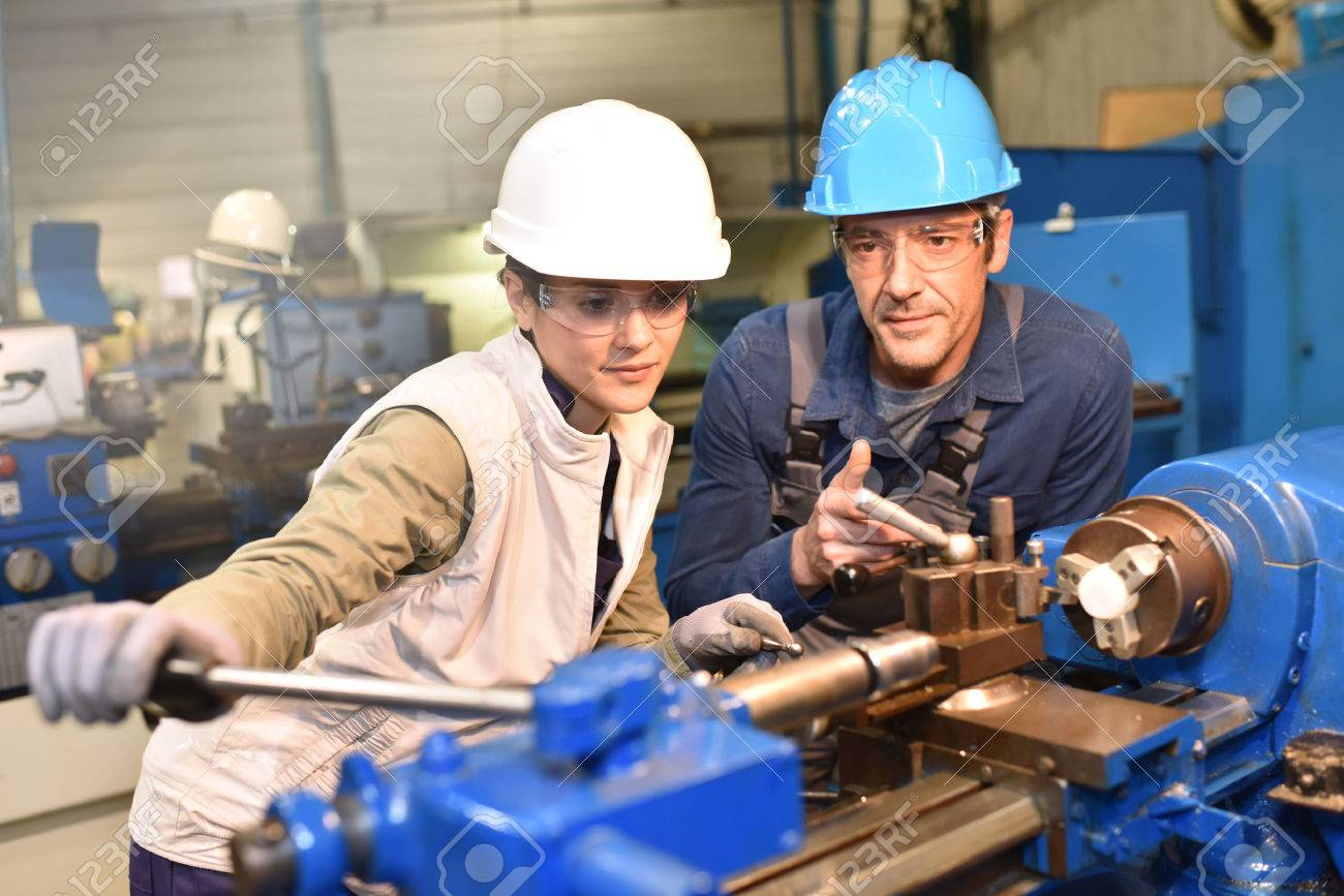 Metal worker teaching trainee on machine use Standard-Bild - 50630766