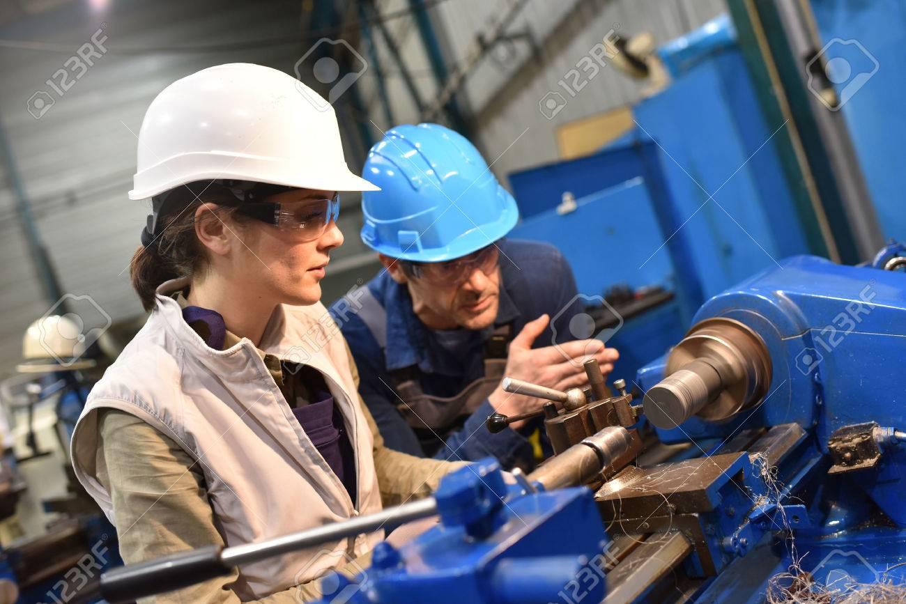 Metal worker teaching trainee on machine use - 50630892