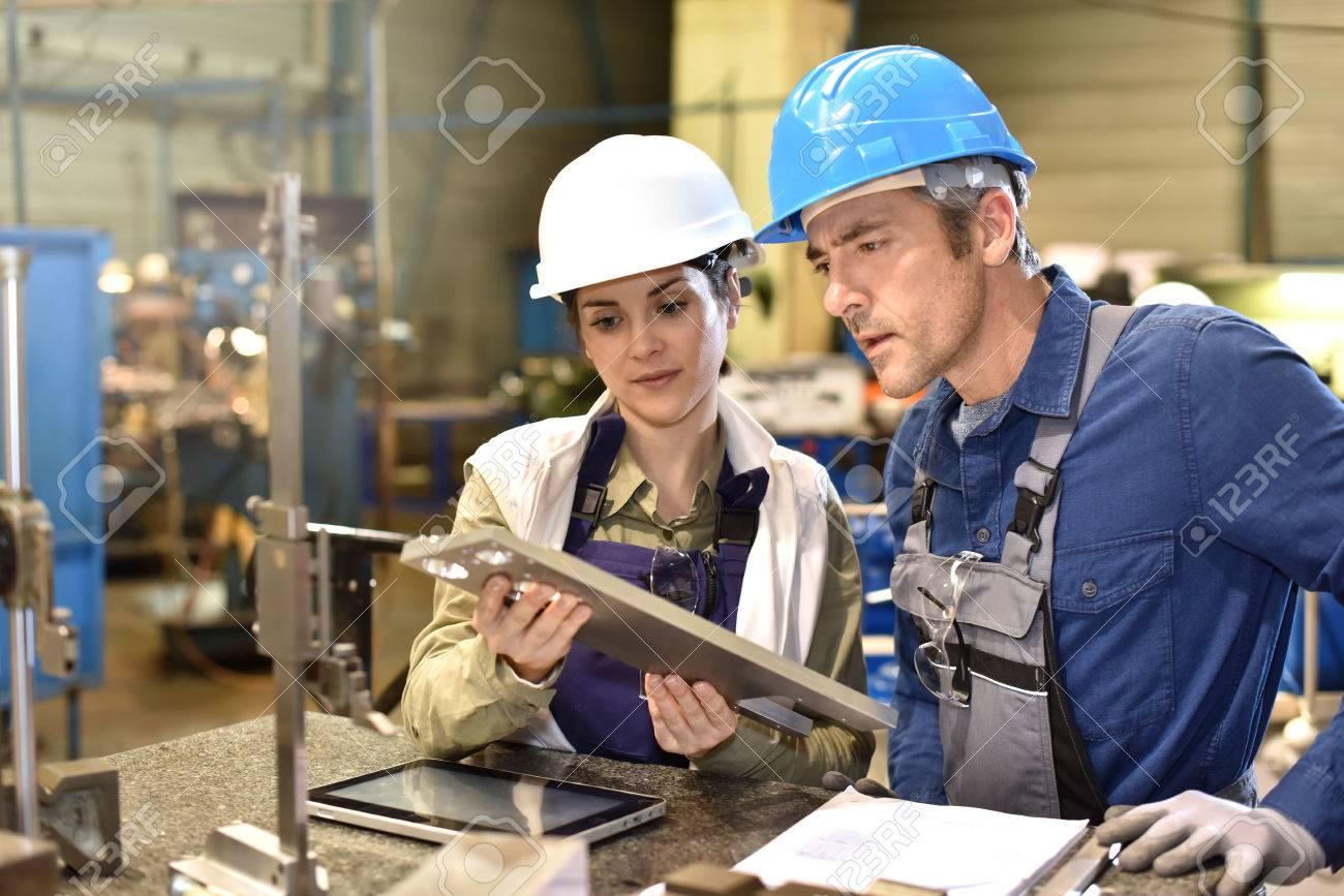 Metallurgy workers in workshop using digital tablet - 50631052