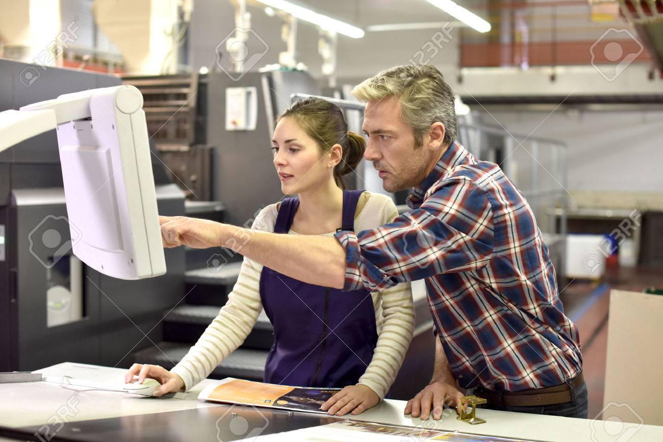 Man working with apprentice in printing house Standard-Bild - 50961618