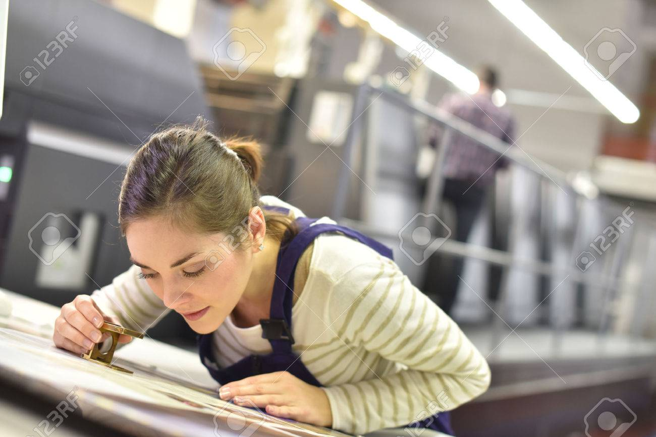Woman in printing house using magnifying glass Standard-Bild - 50961620