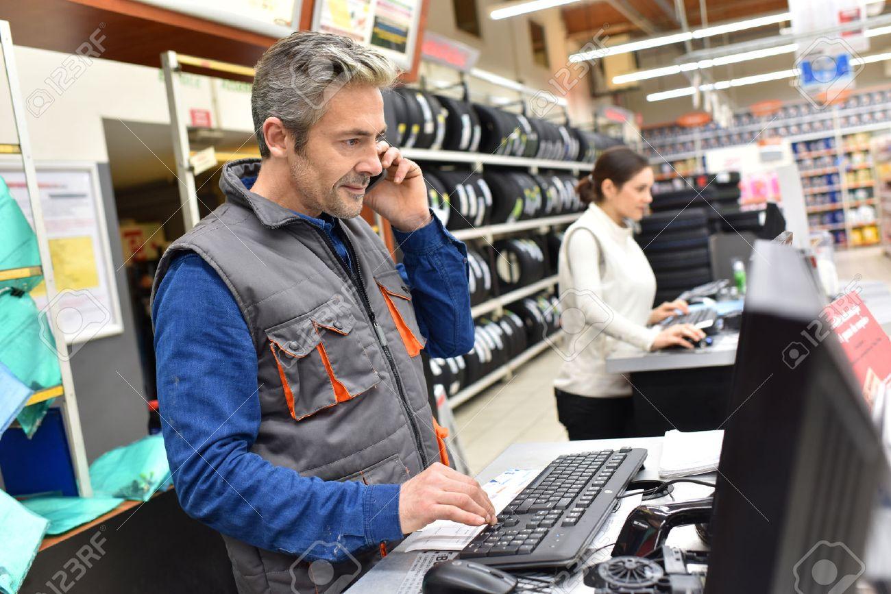 Mechanic in car repair shop talking on phone Standard-Bild - 51015342