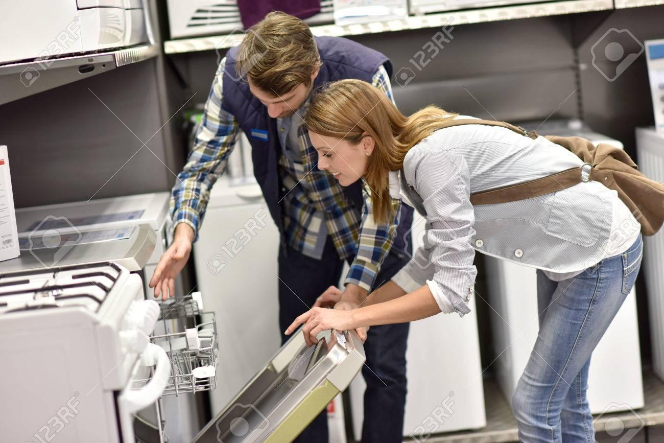 Seller helping customer with choosing dishwasher - 52822261