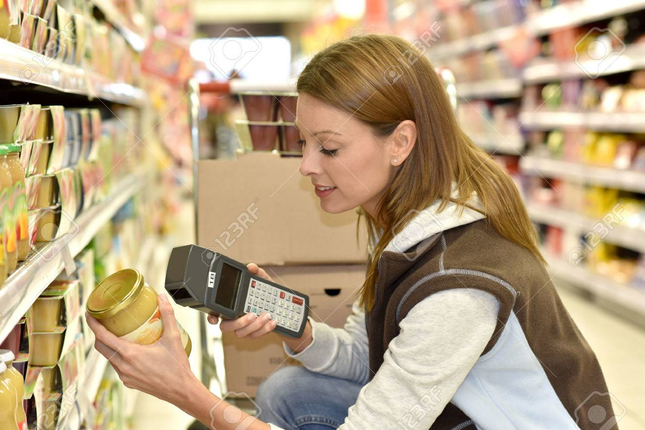 Sales assistant scanning products before putting them on shelves Standard-Bild - 51882092