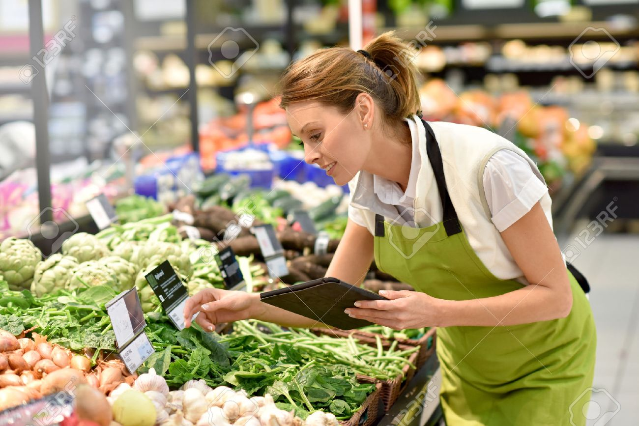 Supermarket employee putting vegetables in shelves Standard-Bild - 51881718