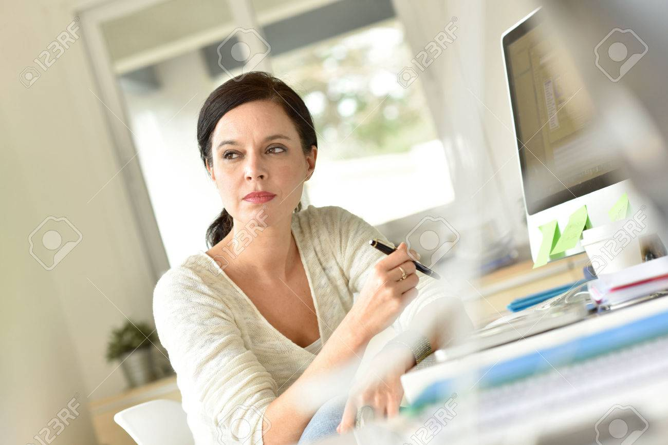Woman in office with a thoughtful look Banque d'images - 54097043