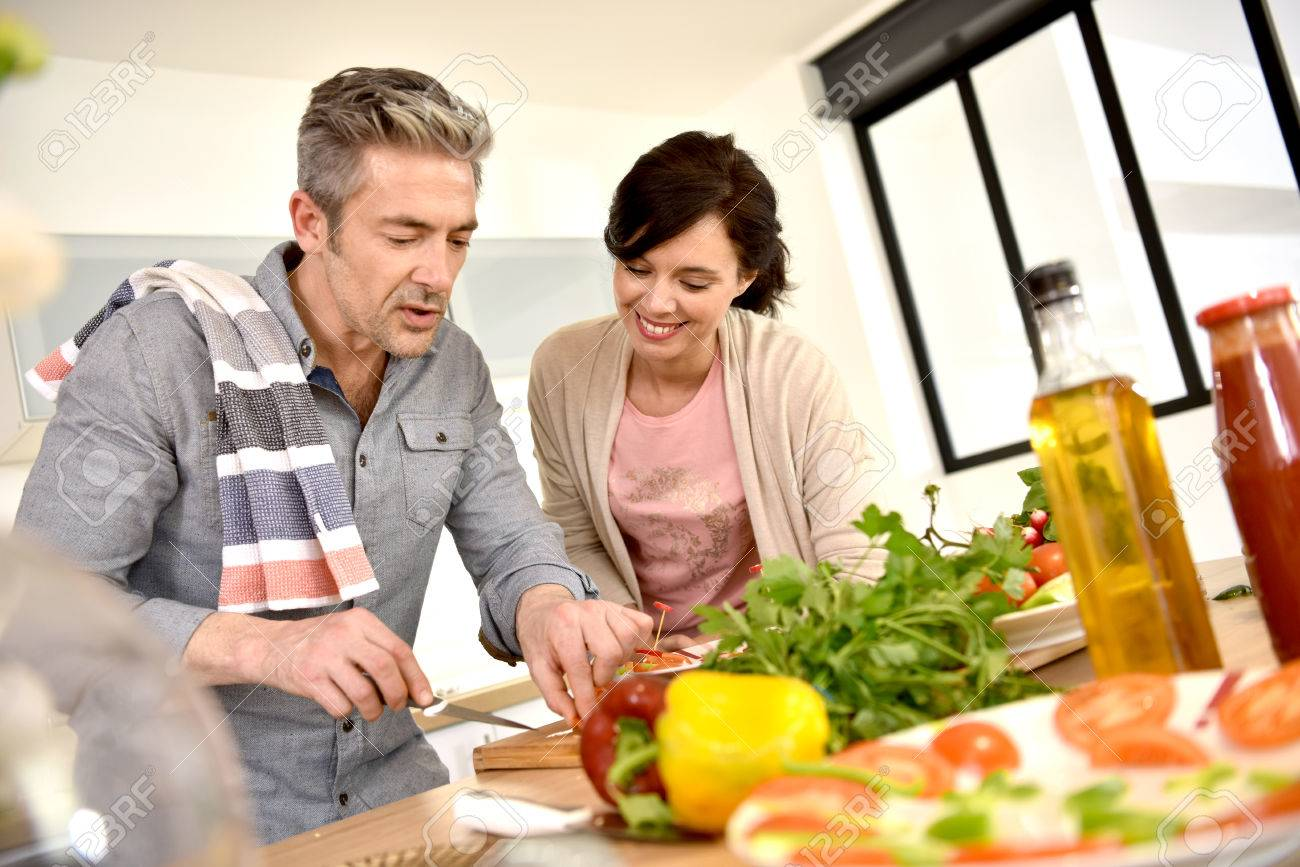 Middle-aged couple having fun cooking together Standard-Bild - 54112222