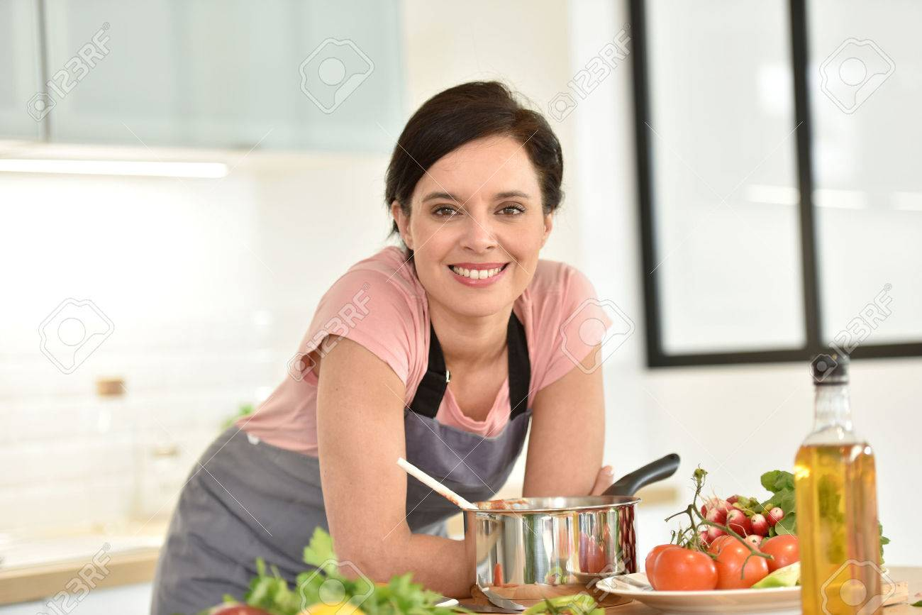 Portrait of beautiful woman cooking in home kitchen - 54113526