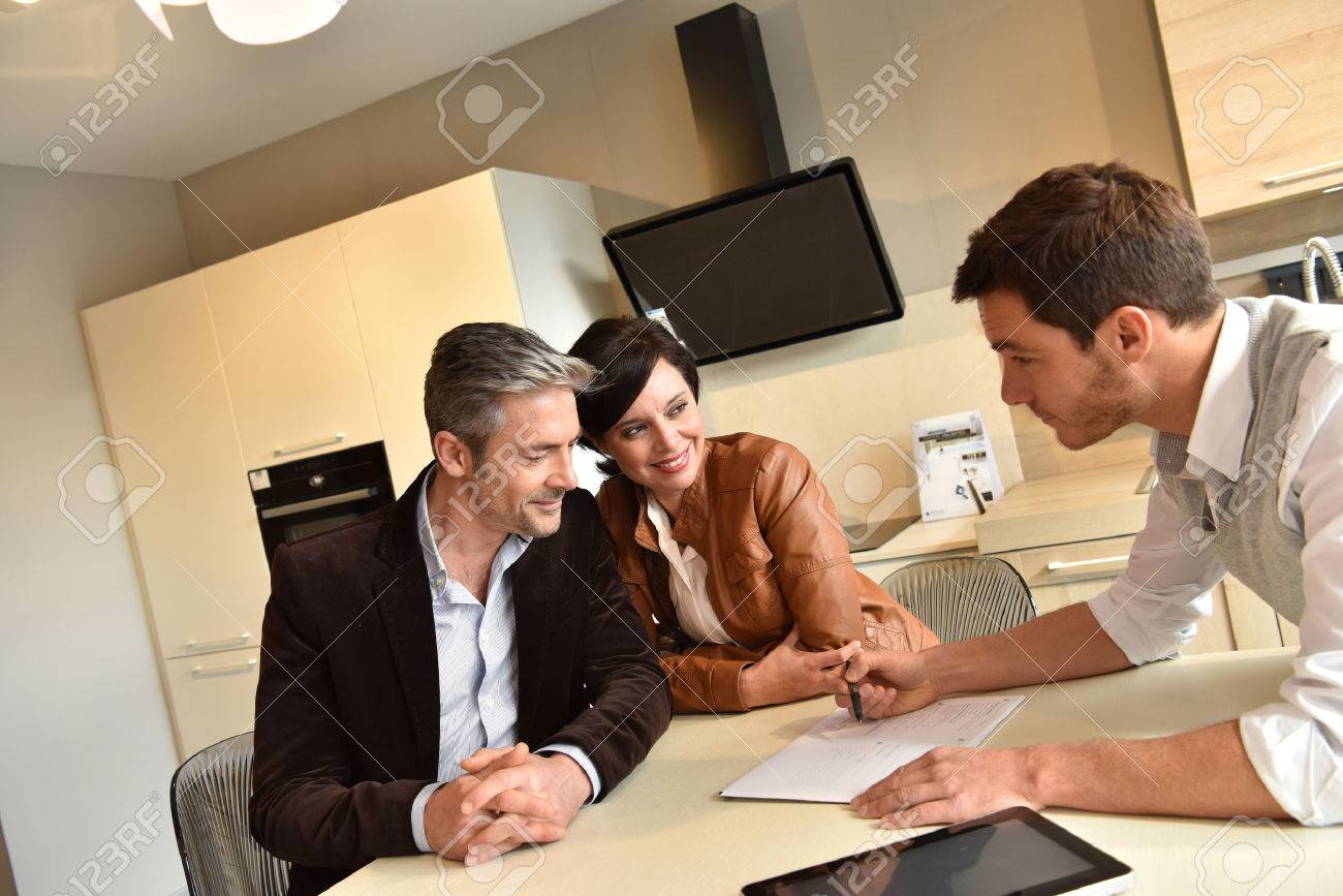 Couple choosing kitchen furniture and getting quotation Banque d'images - 54120765