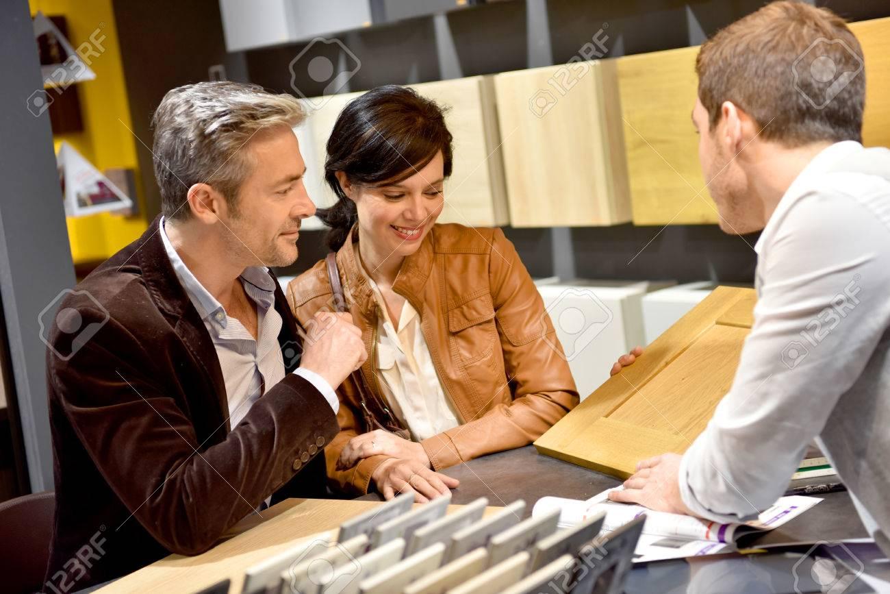 Couple with salesman in kitchen furniture store Standard-Bild - 54120828