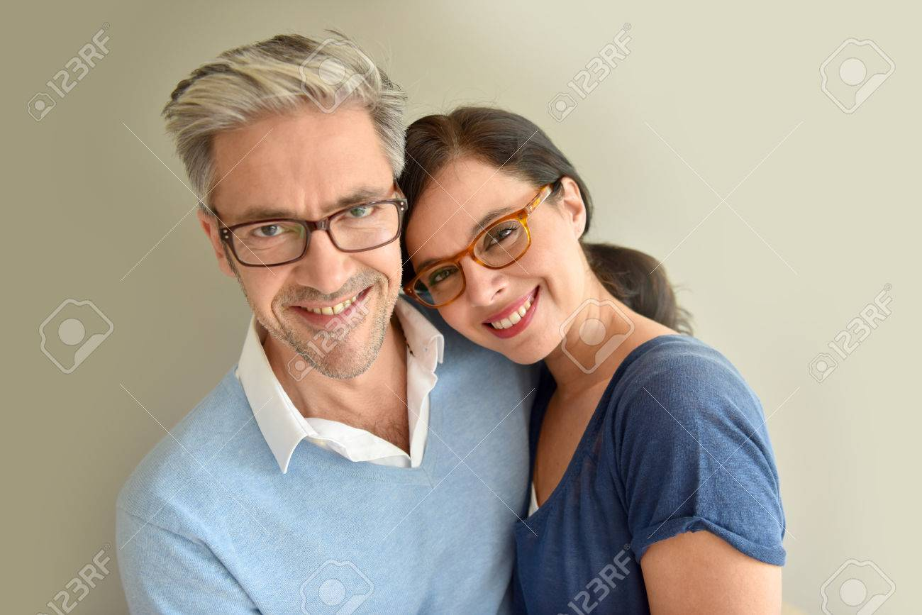 Middle-aged couple with eyeglasses on beige background Standard-Bild - 54120869