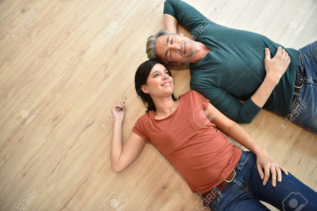 Upper view of couple laying on wooden floor Banque d'images - 54121016