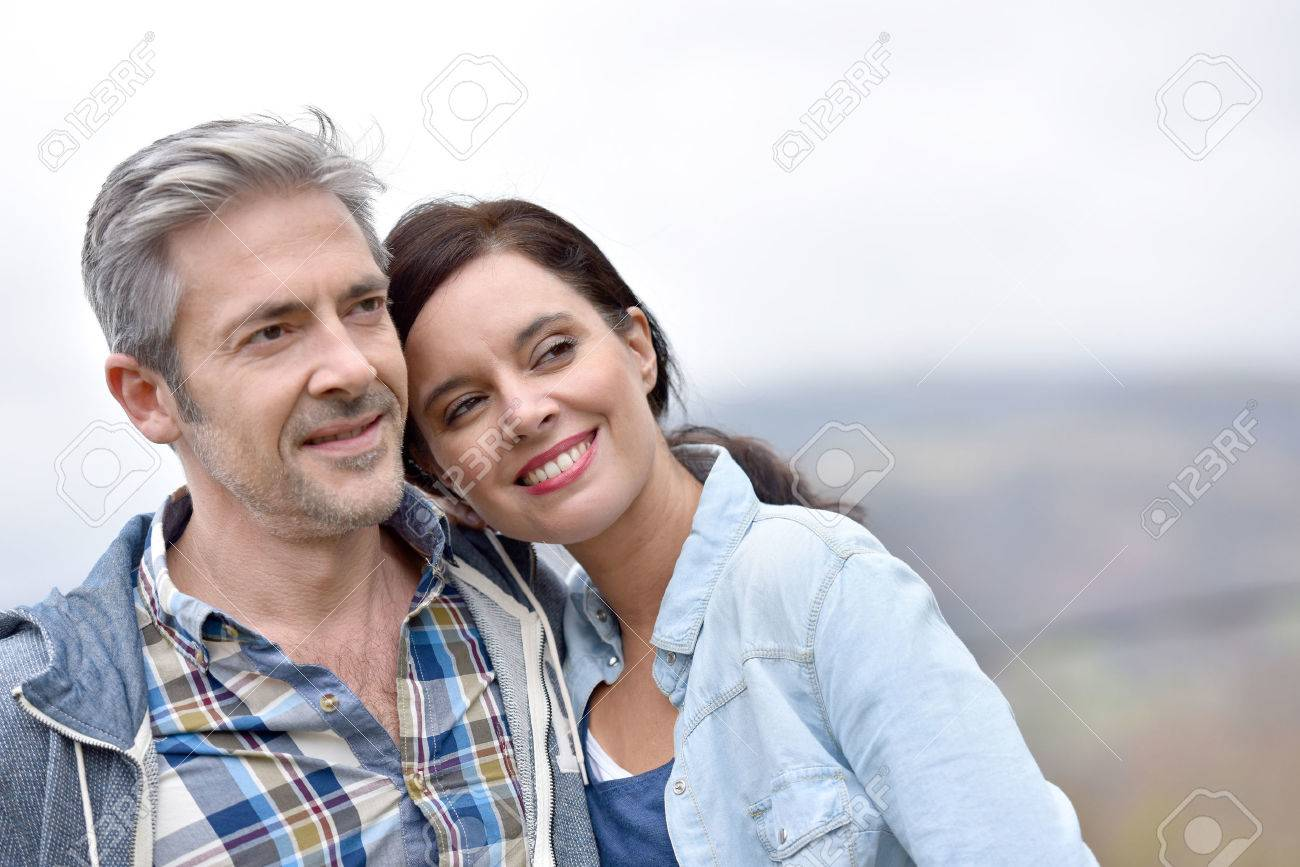 Cheerful middle-aged couple embracing outside Standard-Bild - 54121090