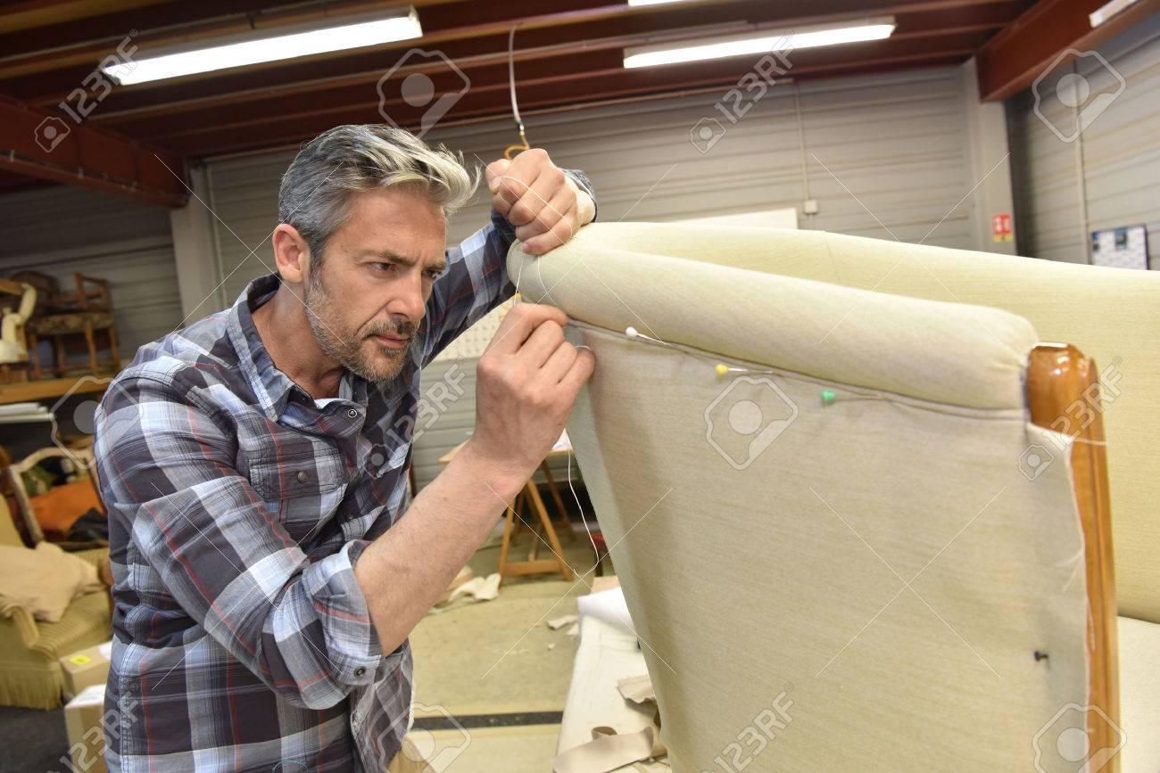 Man working in upholstery workshop Standard-Bild - 55298746