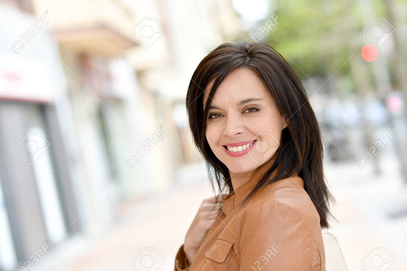 Smiling active woman walking in street Standard-Bild - 55595191