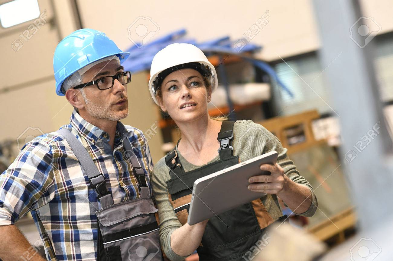 Engineers in warehouse checking stock with tablet Standard-Bild - 57025641