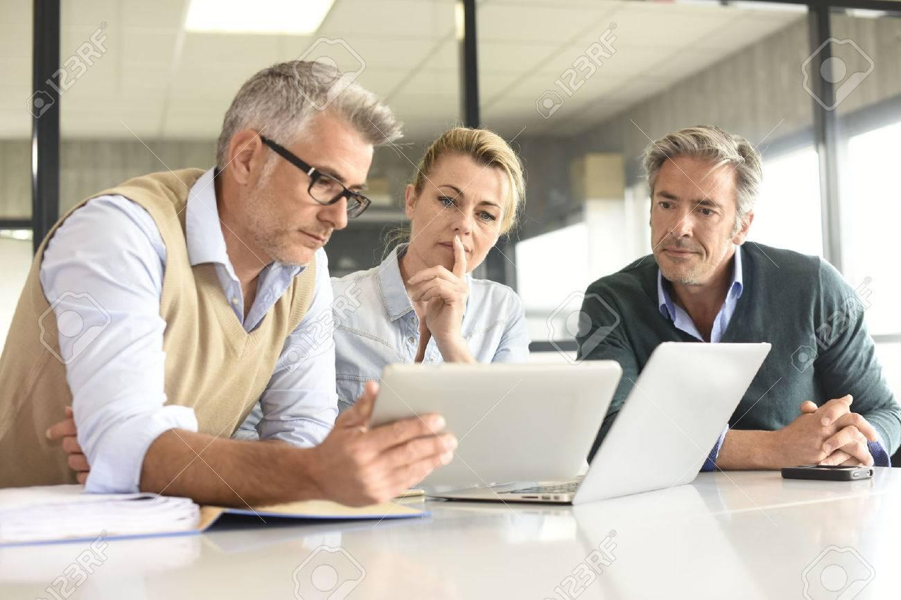 Geschäftsleute in einer Sitzung mit dem Tablet Standard-Bild - 57177256