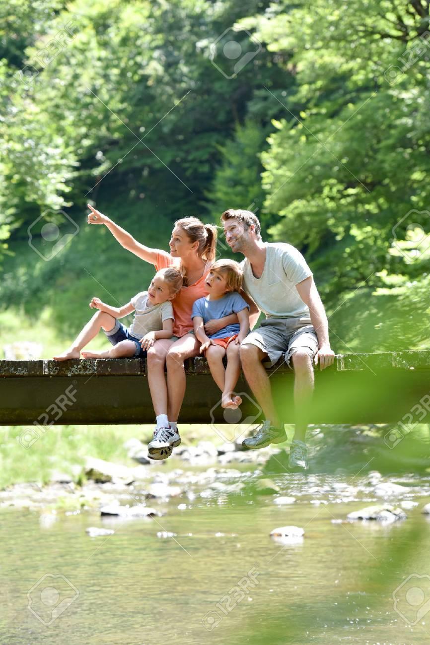Famille assis sur une rivière de montagne traversant le pont Banque d'images - 64862197