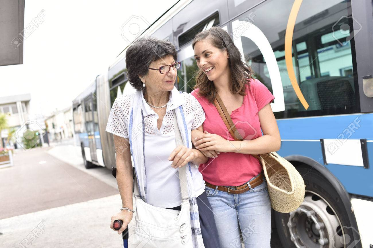 Senior woman with home carer getting off the bus Banque d'images - 60226964