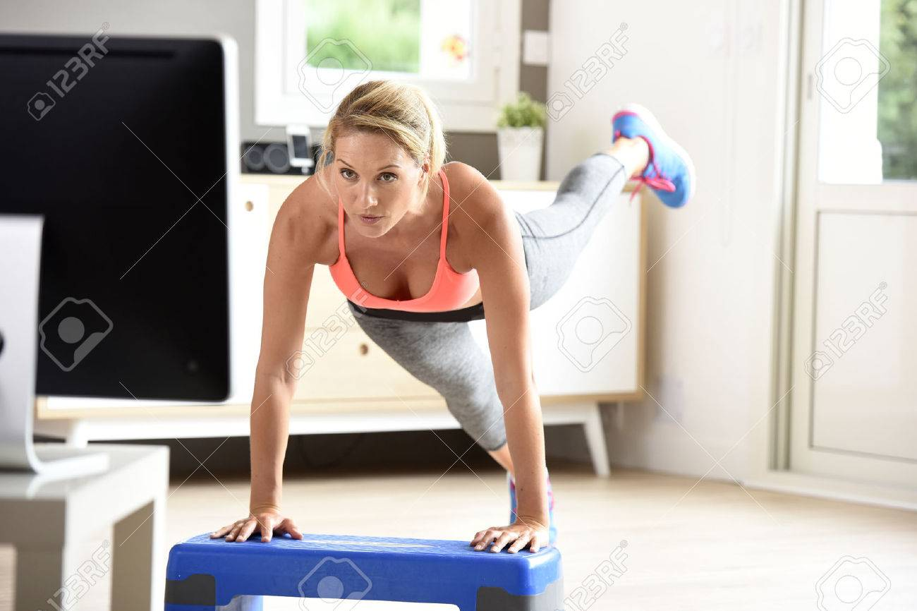 Fitness girl doing exercises in front of TV Banque d'images - 65781943