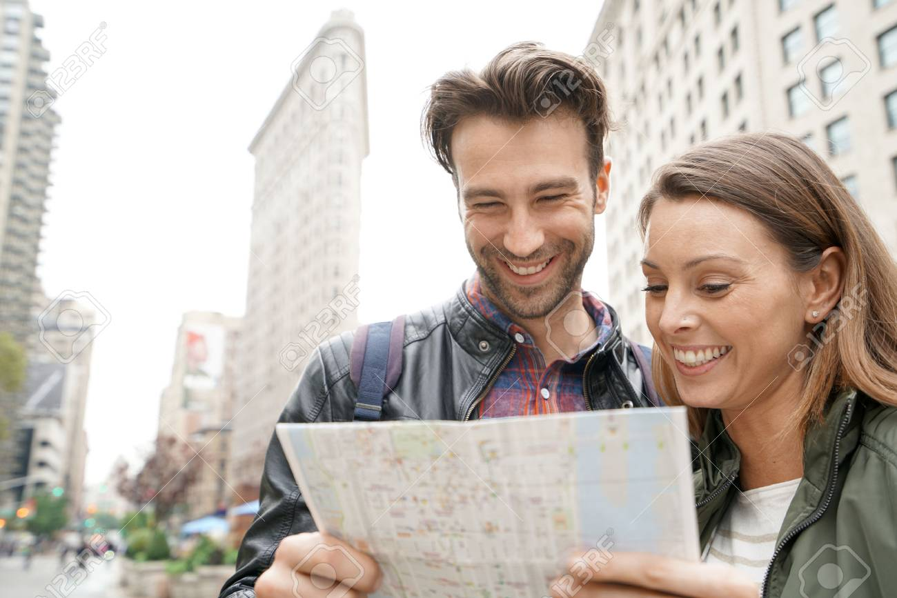 couple in new york city looking at tourist map by flatiron stock photo 65842202