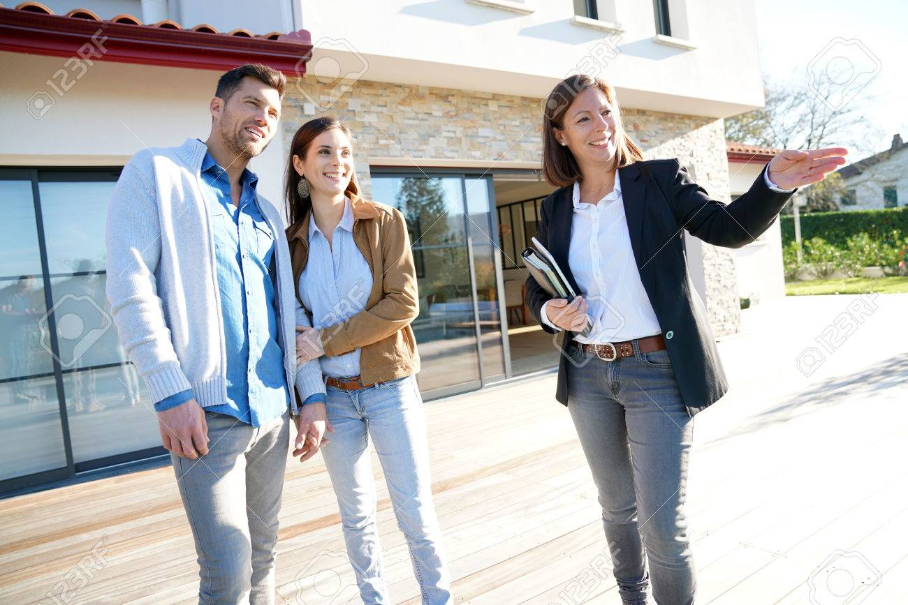 Paare mit Immobilienmakler Besuch Haus zum Verkauf Standard-Bild - 67348937