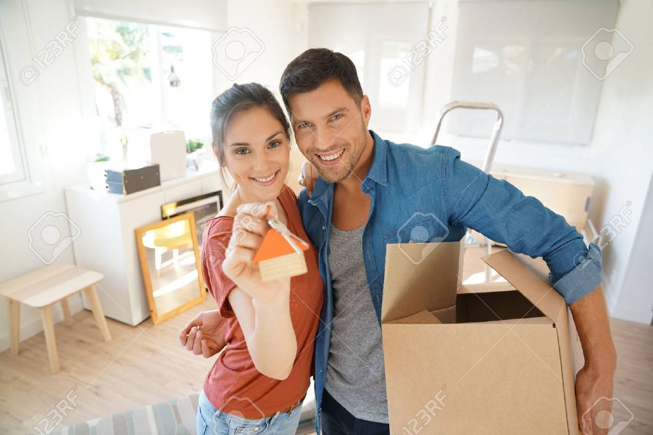 Glückliches Paar, das Schlüssel des neuen Hauses zeigt Standard-Bild - 67349000
