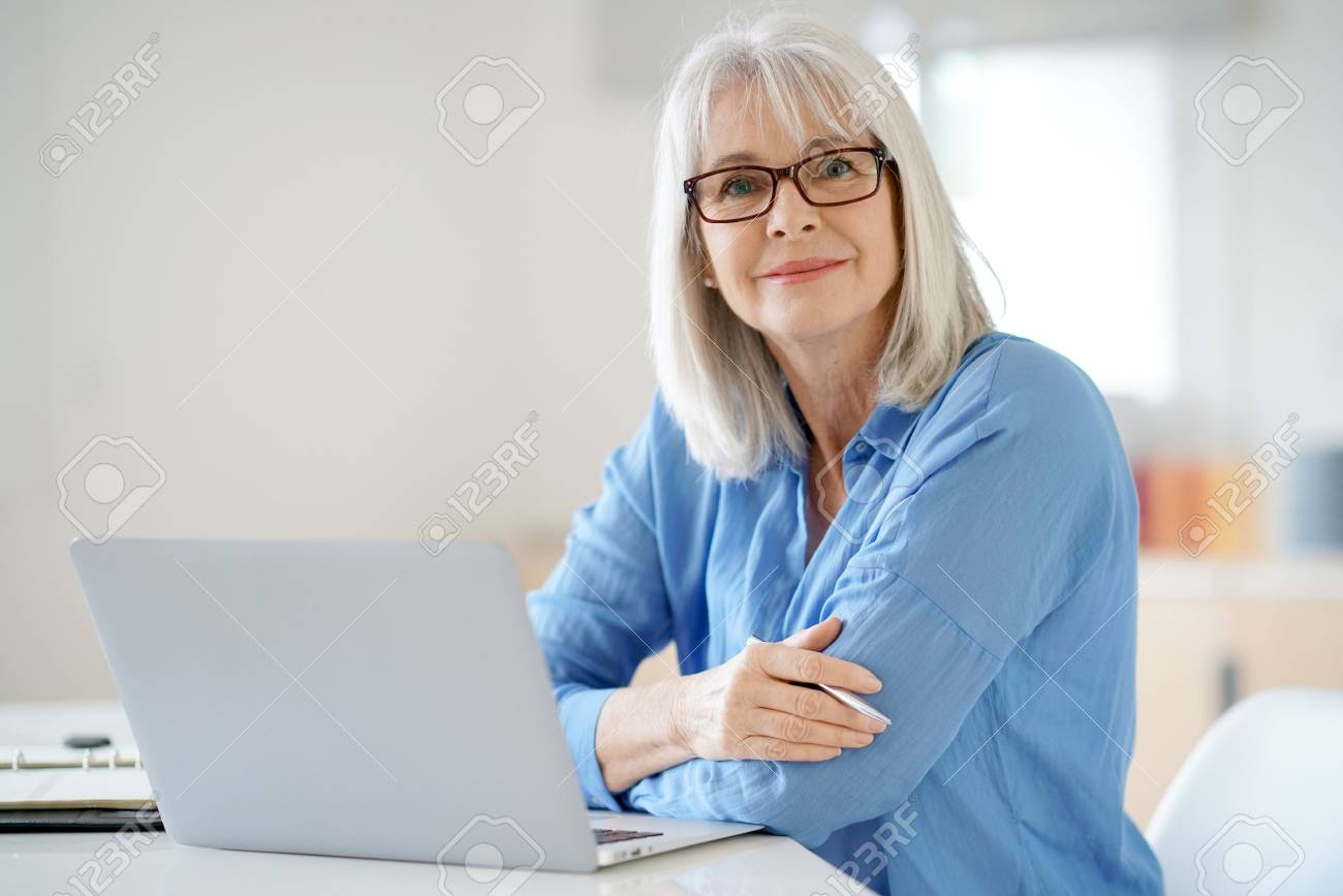 Senior businesswoman working in office - 69034031