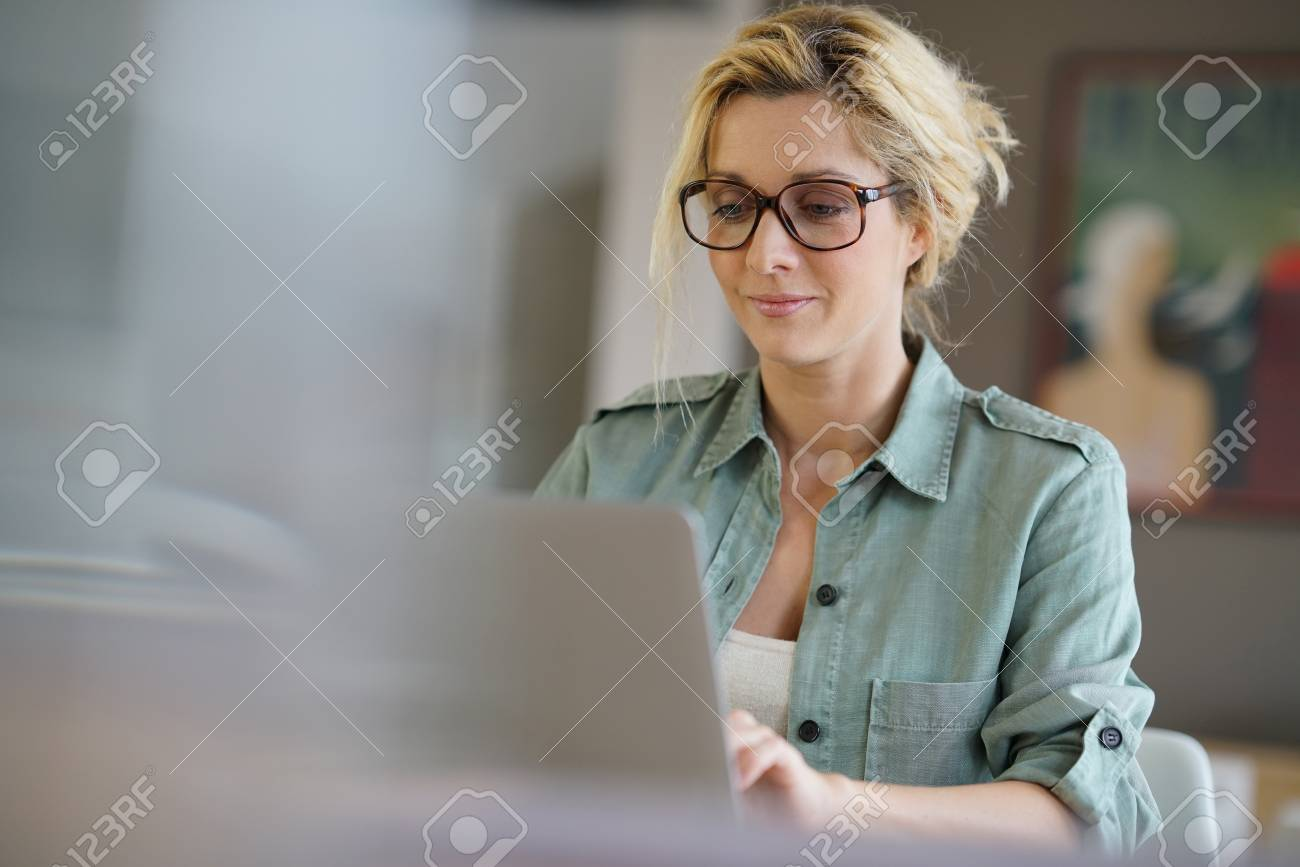 Portrait of blond woman working from home on laptop computer - 71634240