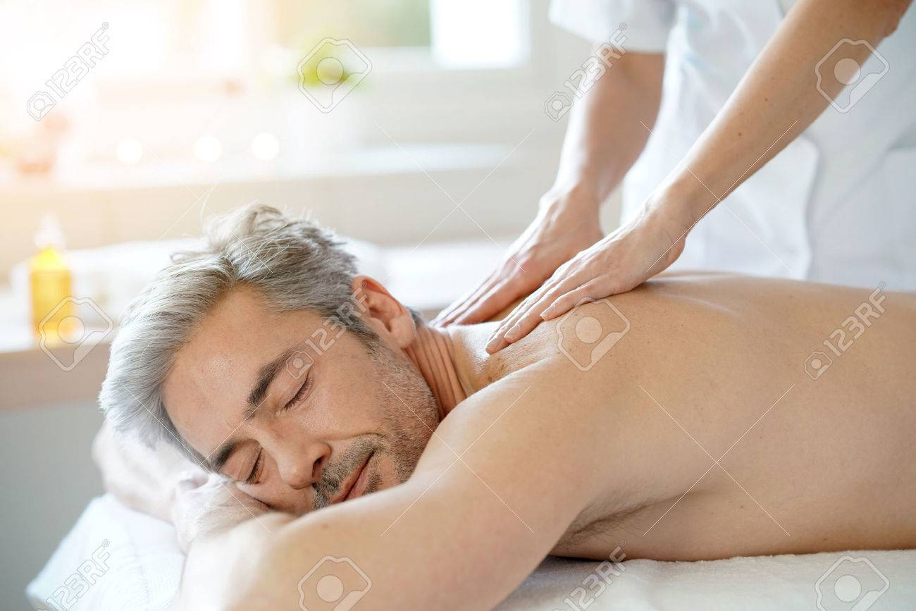 Man relaxing on massage table receiving massage Standard-Bild - 71851336