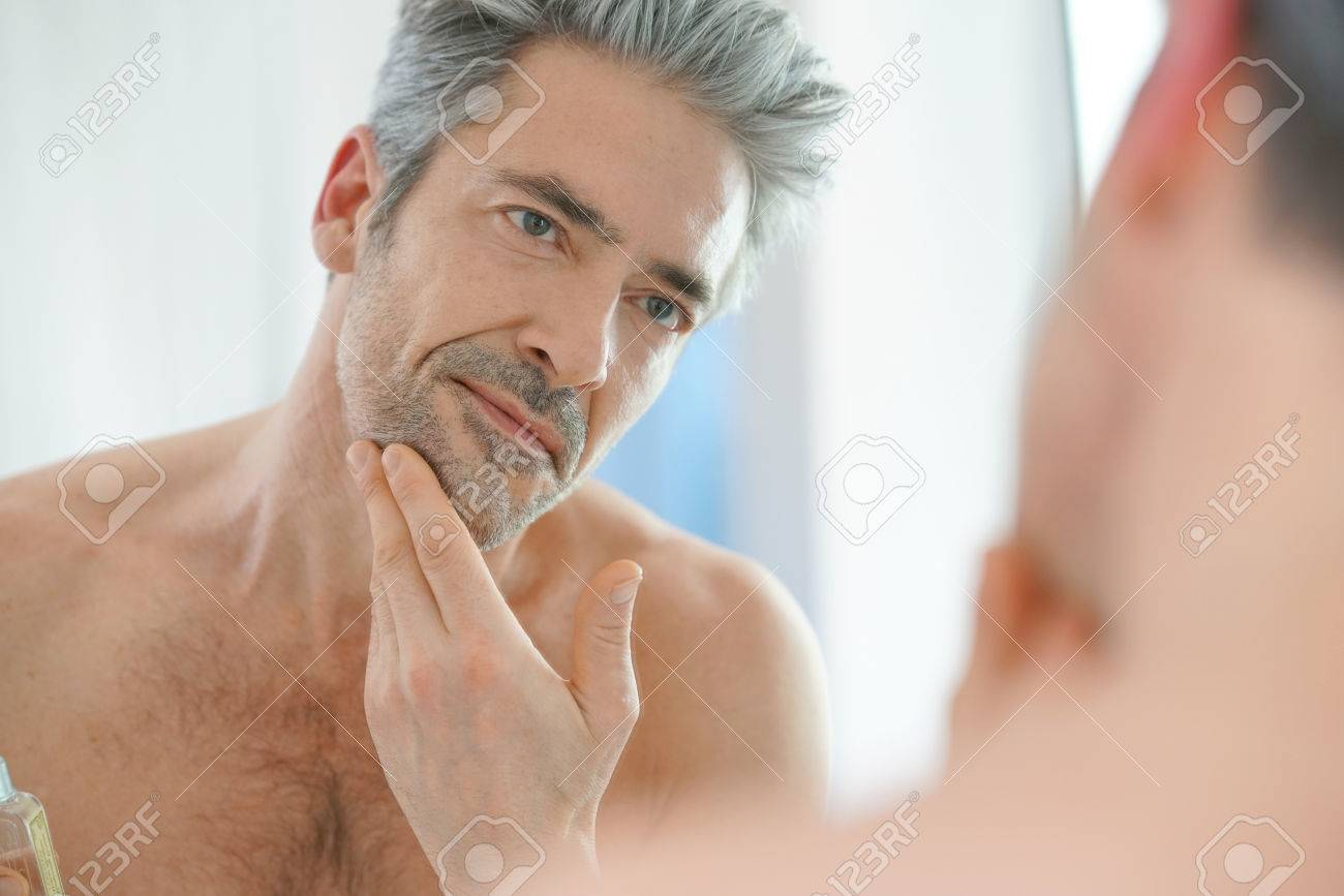 Portrait of mature man in front of mirror applying facial cream Banque d'images - 71860900
