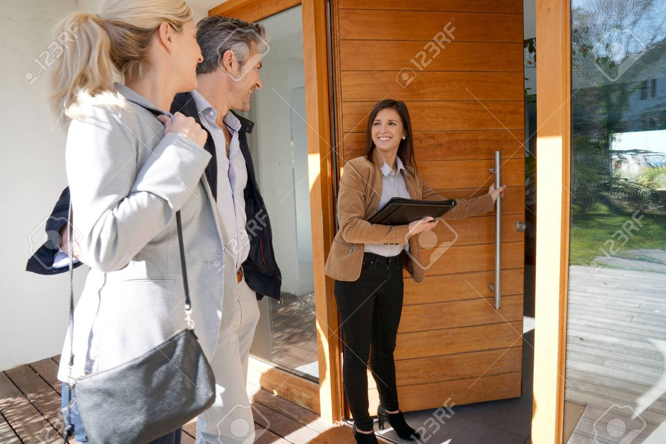 Real estate agent inviting couple to enter house for visit - 71860877