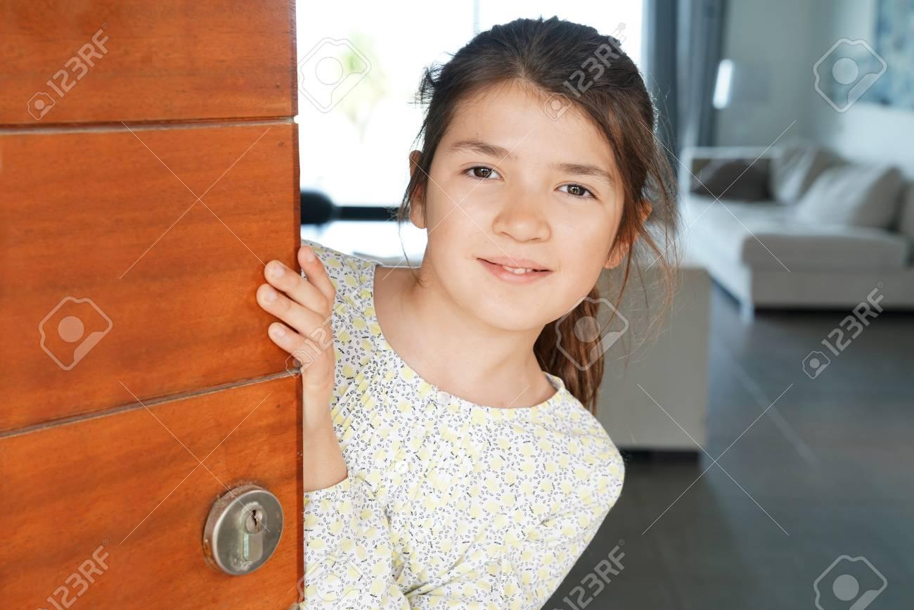 opening front door. Portrait Of Young Girl Opening Front Door The House Stock Photo - 74819382