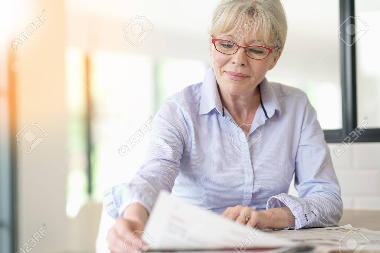 senior woman with eyeglasses reading newspaper at home stock photo
