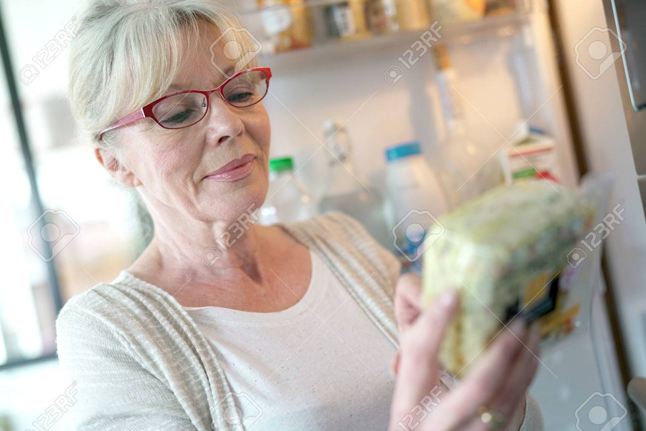 Senior woman checking expiration date on food product - 76362106