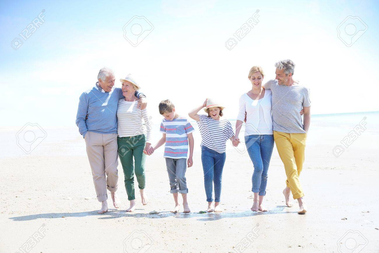 Family, parents, grandparents and grandkids walking on the beach - 77443206