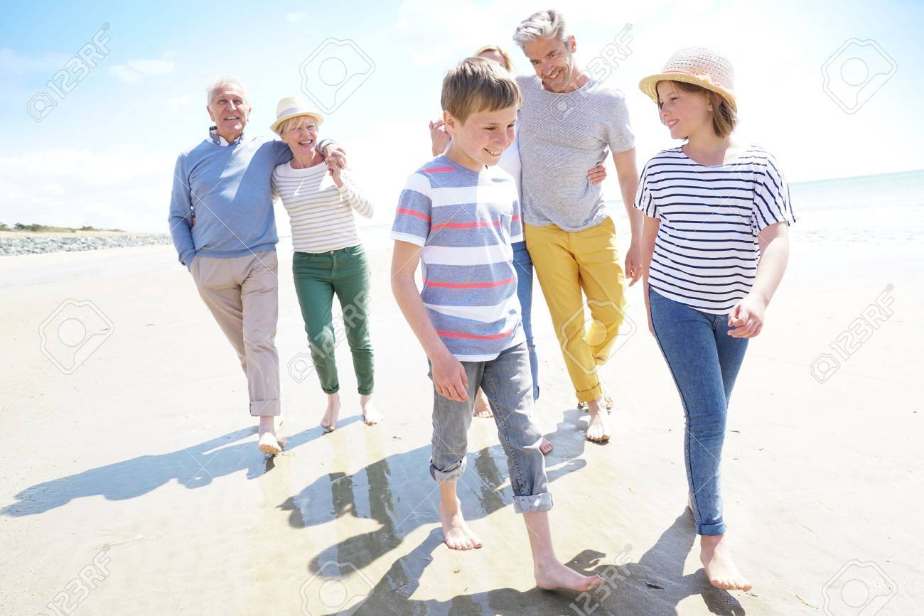 Happy intergenerational family walking on the beach - 77443198