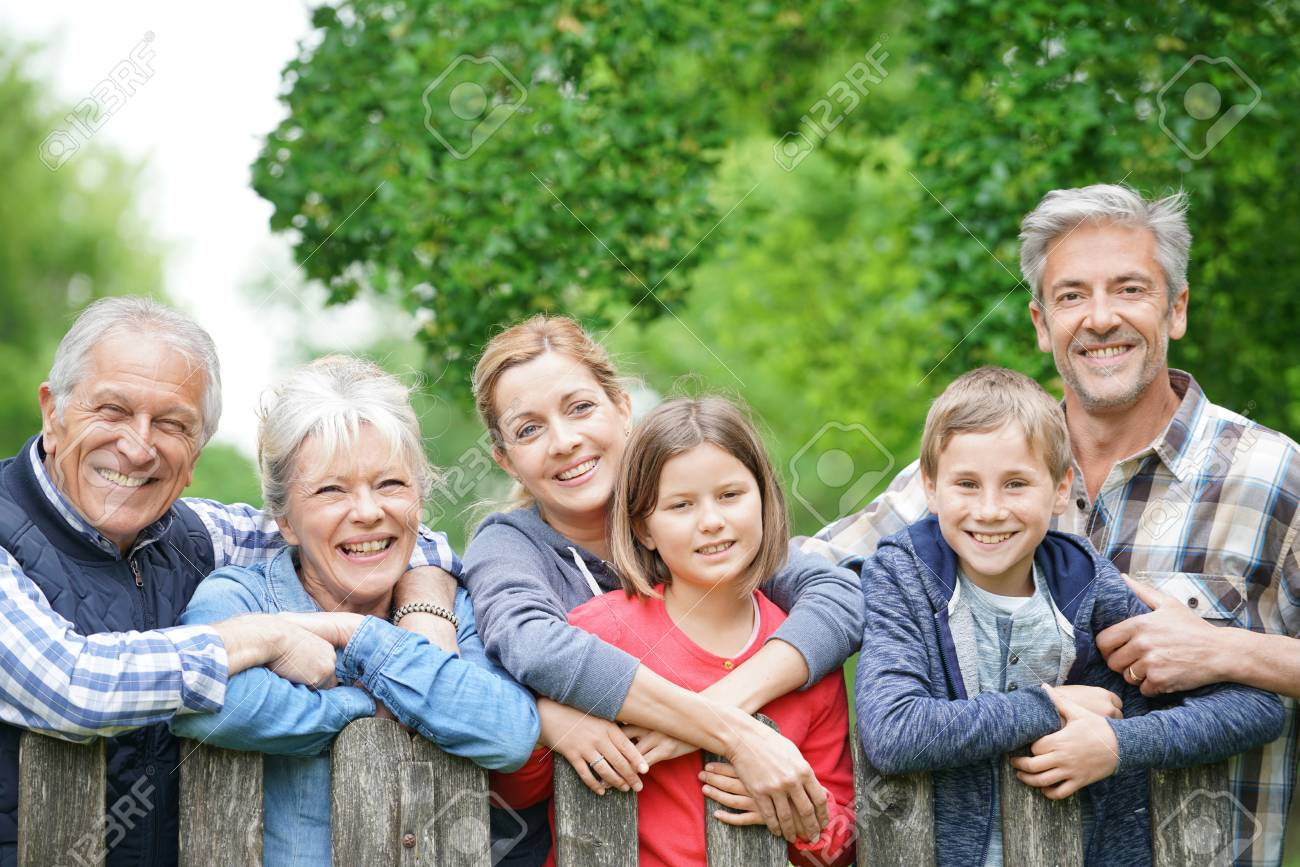 Portrait of happy family leaning on fence - 77416617