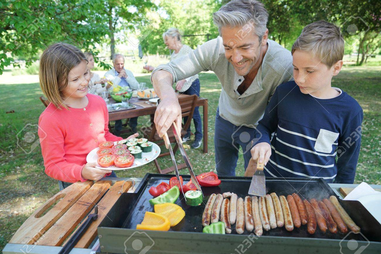 Father with kids preparing barbecue for family lunch - 77475480