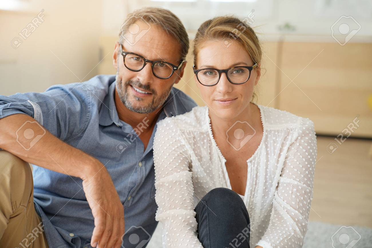 Mature couple with eyeglasses sitting on carpet at home - 86417205